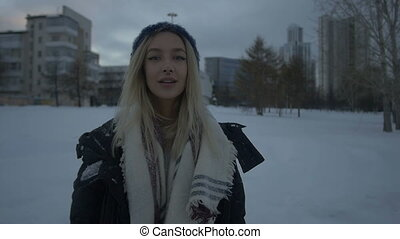 Beautiful girl standing outdoors in the snow