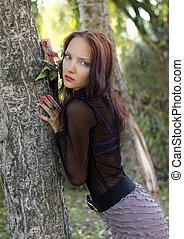 Beautiful girl stands near a tree