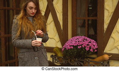 beautiful girl stands on a street and drink coffee -...