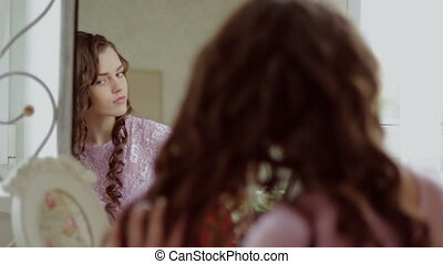 Beautiful girl stoke your hair in front of mirror HD