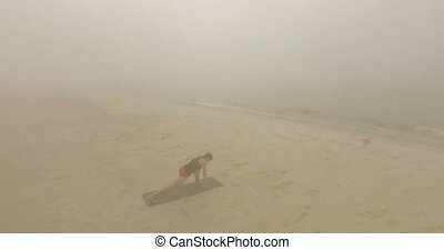 Beautiful Girl Stretches Her Legs on a Sandy Beach at foggy weather.