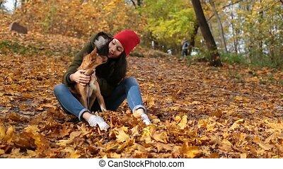 Beautiful girl stroking cute dog in autumn park