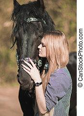 beautiful girl stroking horse outside - young beautiful girl...