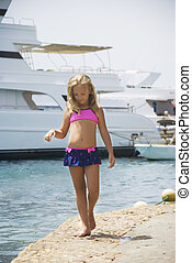 Beautiful girl strolls along the shore of the stone on the background of yachts
