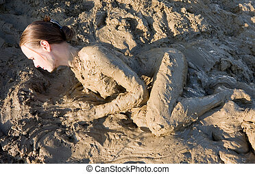 Beautiful girl struggling in the mud. very dirty