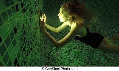 Beautiful girl swim underwater into night waterpool with...
