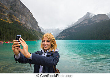 Beautiful girl taking a selfie in the mountains
