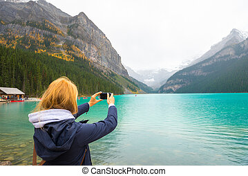 Beautiful girl taking photos in the mountains