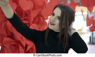 Beautiful girl taking selfie on a background of red hearts. Happy. Slowly