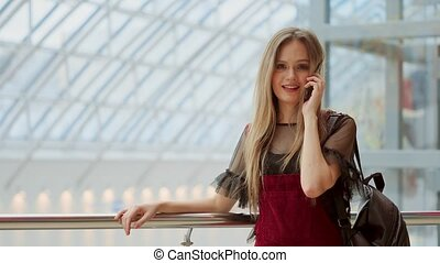 Beautiful girl talking on a mobile phone looking at the camera and smiling. beautiful girl talking on smartphone and sitting with shopping bags in mall