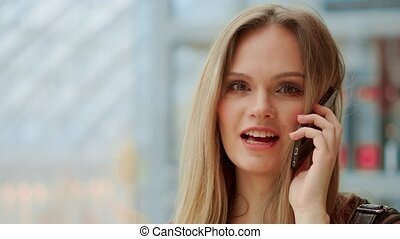 Beautiful girl talking on a mobile phone looking at the...