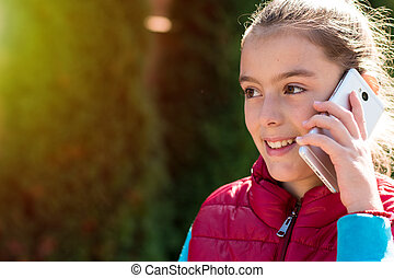 Beautiful girl talking on a smartphone in red vest