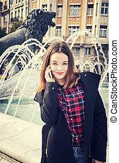 Beautiful girl talking on mobile phone in urban city