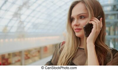beautiful girl talking on smartphone and sitting with shopping bags in mall