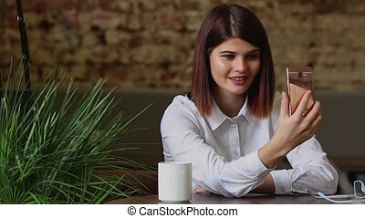 Beautiful girl talking to business partners using a mobile phone camera.