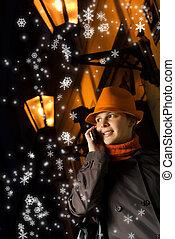 Beautiful girl talks on the phone at Christmas night