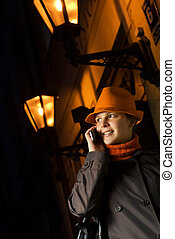 Beautiful girl talks on the phone in european city