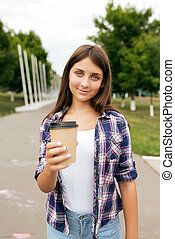 Beautiful girl teenager 11-12 years old, standing in summer city park. Happy smiles, holds out her hand with cup of coffee or tea. Concept of an offer to drink. Treats and appeals to remove thirst.