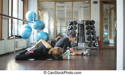 beautiful girl the trainer makes stretching muscles of the legs, the man next to her student. She athlete fintnes instructor.