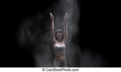 Beautiful dancer in top and shorts throwing white dust in the dark - slow motion video