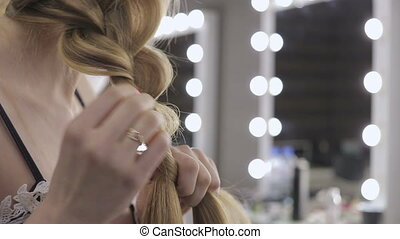 Beautiful girl ties her hair in pigtails, beauty care...