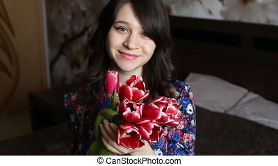 beautiful girl to sniff flowers, looking at the camera, smiling, flirting.