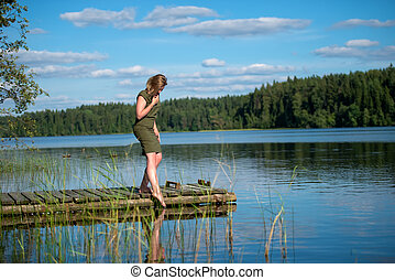 Beautiful girl touches the water standing on a wooden jetty at a lake