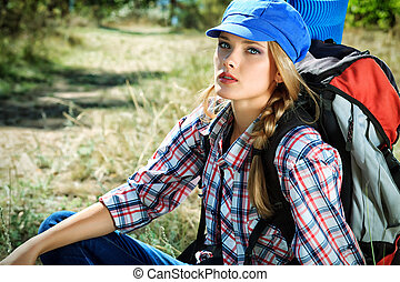 trekking - Beautiful girl tourist having a rest on a...