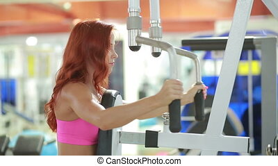 Beautiful girl trains in the gym.