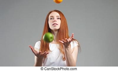 Beautiful girl tries to choose orange or apple. Healthy food...