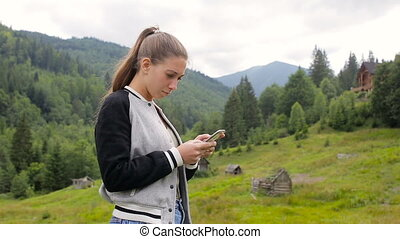 Beautiful girl uses a phone in the background of a forest and a mountain village