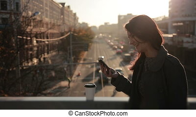 beautiful girl uses a smartphone on a city bridge