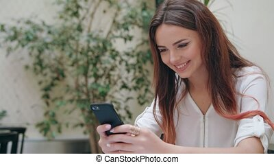 Beautiful Girl Using a Mobile Phone in the Room