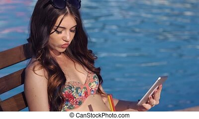 Beautiful girl using a tablet and suntanning near pool. She...