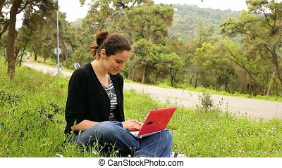 beautiful girl using computer in countryside, bicycles passing behind