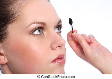 Beautiful girl using eye lash separator brush