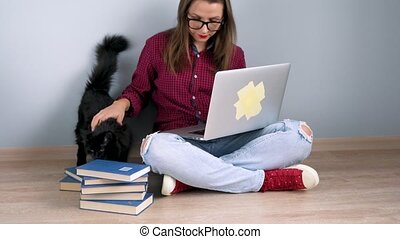 Beautiful girl using laptop and stroking a black cat while sitting on the floor at home