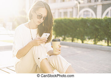 Beautiful girl using phone while sitting with cup of coffee.