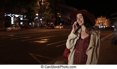 Beautiful girl using smortphone on street at night