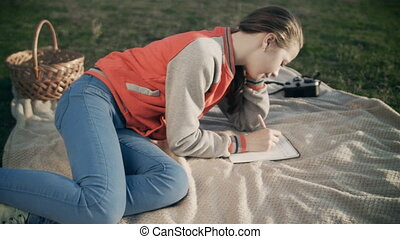 Beautiful girl using tablet or ebook outdoor laying on...
