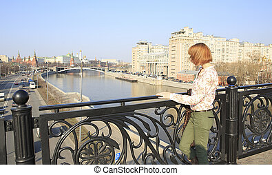 Beautiful girl walking around Moscow (stopped on the bridge).
