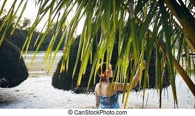 Beautiful girl walking around the palm trees