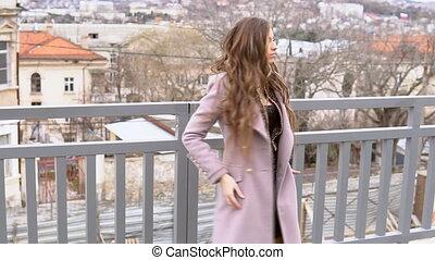 beautiful girl walking in the coats on the street