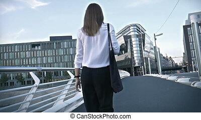 Beautiful girl walking on a bridge in a busy city center