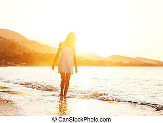Beautiful girl walking on the beach at sunset, freedom concept