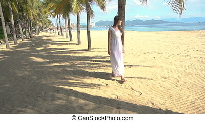 Beautiful girl walking on the beach between palms. Young brunette woman in white long dress at the sea shore in Vietnam.