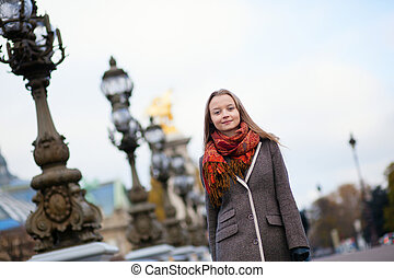 Beautiful girl walking on the Pont Alexandre III in Paris