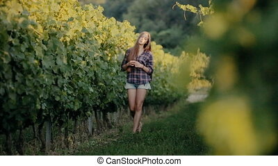 Beautiful girl walking on the vine rows
