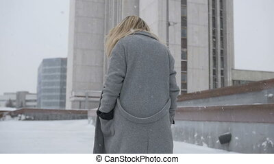 Beautiful girl walking through the city in winter