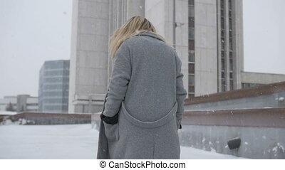 Beautiful girl walking through the city in winter